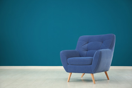 Comfortable armchair against color wall in empty room Imagens