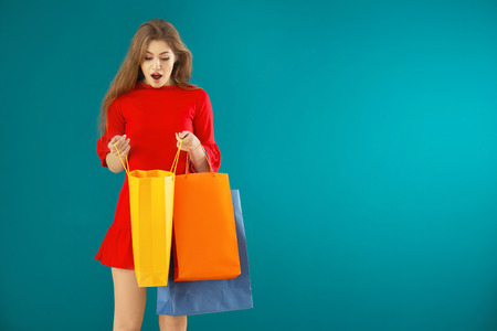 Surprised young woman looking inside of shopping bag on color background