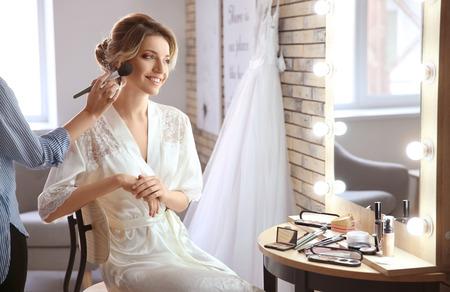 Makeup artist preparing bride before her wedding in room Foto de archivo - 112779967