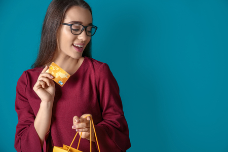 Beautiful young woman with shopping bag and credit card on color background 写真素材