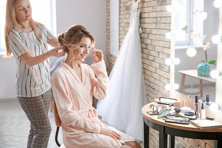 Hairdresser preparing bride before her wedding in room