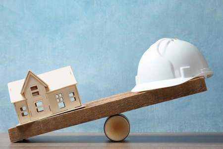 Model of house and builders hard hat on wooden scales. Concept of balance between work and personal life Stok Fotoğraf