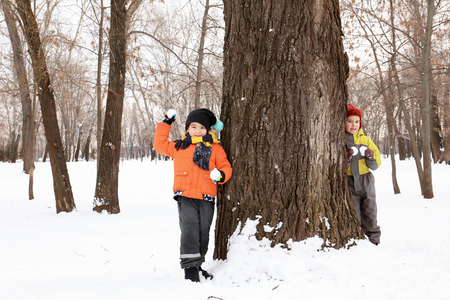 Children playing in snowy park on winter vacation