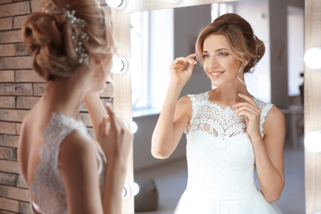 Beautiful young bride in white wedding dress with makeup created by professional artist near mirror indoors