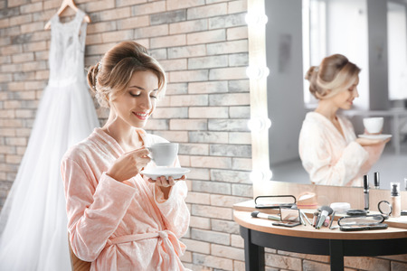 Beautiful young bride drinking coffee in makeup room