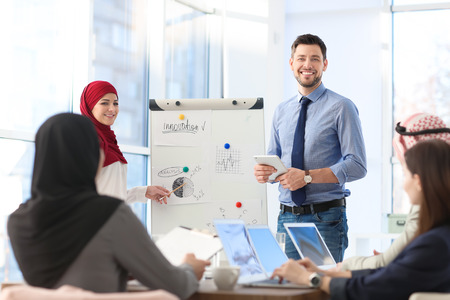 Muslim businesswoman and her coworker showing presentation on meeting Stock Photo