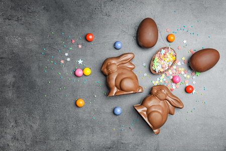 Chocolate Easter bunnies and candies on grey background