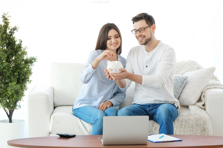 Young couple putting coin into piggy bank at home. Thinking over pension plan