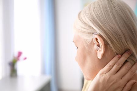 Donna matura con apparecchio acustico al chiuso