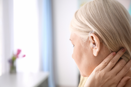 Mature woman with hearing aid indoors Stok Fotoğraf