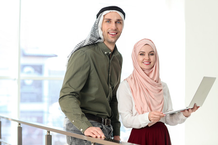 Muslim businessman with coworker in office