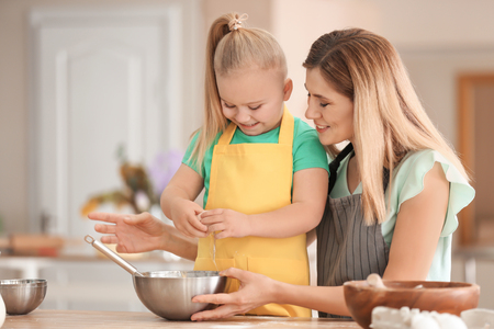Mother with daughter preparing dough together in kitchen
