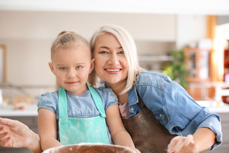 Little girl and her grandmother covered with flour in kitchen