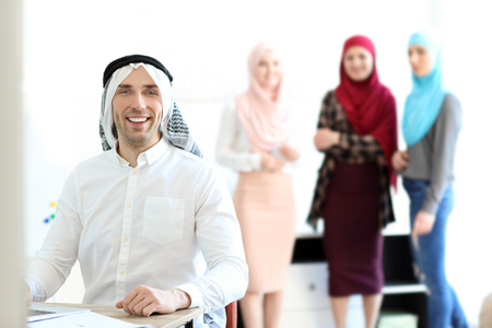 Muslim businessman in traditional clothes at workplace