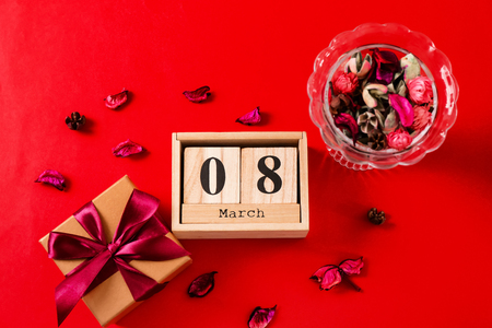 Wooden block calendar, flower petals and gift box on color background. International Women's Day celebration