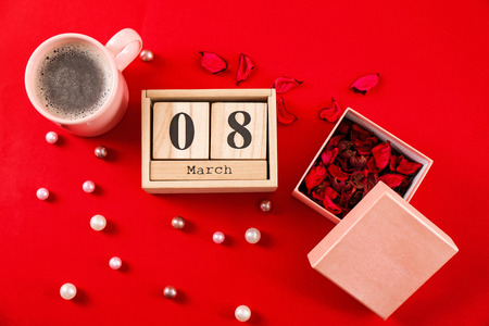 Wooden block calendar, flower petals and cup of coffee on color background. International Women's Day celebration