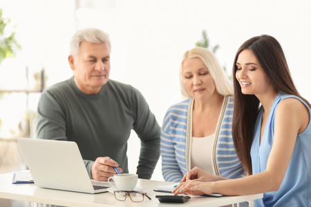 Mature couple discussing pension plan with consultant in office
