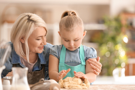 Little girl and her grandmother preparing dough together in kitchen