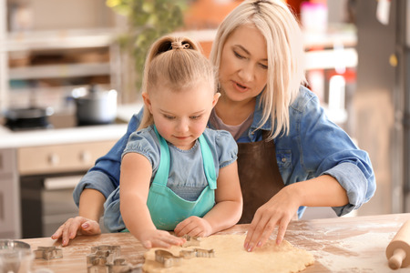 Little girl and her grandmother making cookies in kitchen Stock Photo