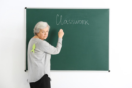 Senior teacher with paper fish on her back writing on chalkboard. April fools day celebration