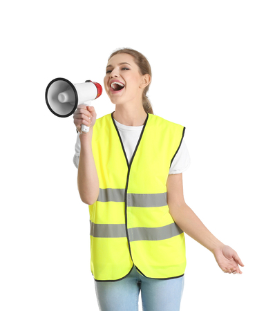 Young woman in reflective vest with megaphone on white background