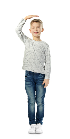 Cute little boy measuring height on white background Stockfoto