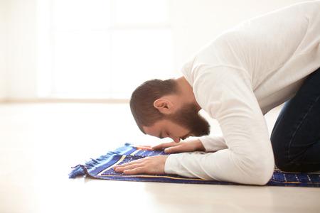 Young Muslim man praying, indoors Stock Photo