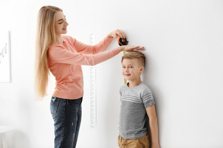 Young woman measuring height of little boy at home Stock Photo