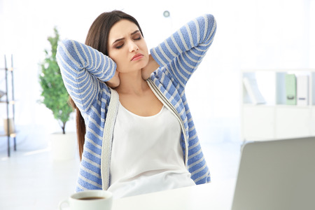 Tired woman at workplace Stock Photo