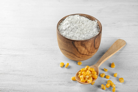 Spoon with kernels and corn starch in wooden bowl on table Фото со стока