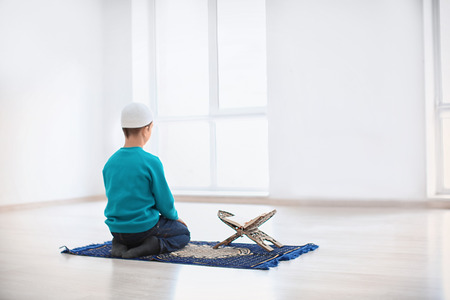 Little Muslim boy praying, indoors Stock Photo