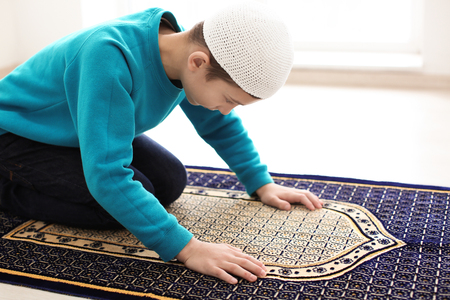 Little Muslim boy praying, indoors Stock Photo