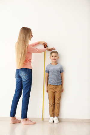 Young woman measuring height of little boy near light wall Stock Photo