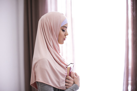 Young Muslim woman holding Koran and praying, indoors Stock Photo