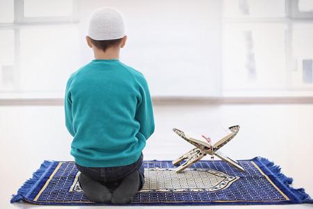 Little Muslim boy praying, indoors Imagens