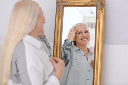 Smiling mature woman standing near mirror at home
