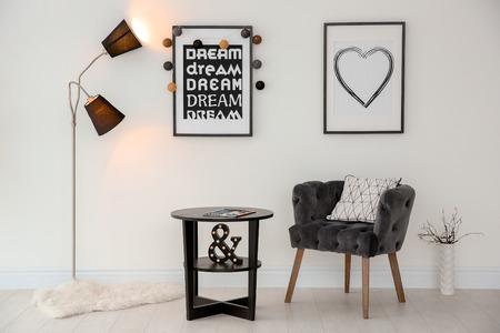 Elegant living room interior with comfortable armchair and stylish floor lamp Stockfoto