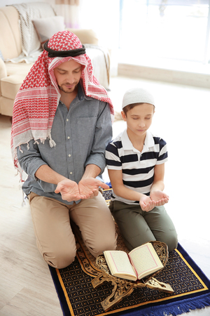 Muslim man praying with son at home Stock Photo