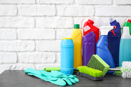 Cleaning supplies and tools on table near brick wall Stock Photo