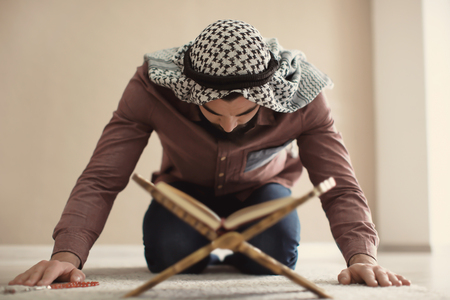 Young Muslim man praying, indoors Imagens