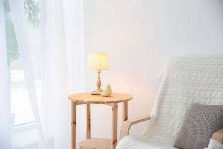 Side table with stylish lamp in living room
