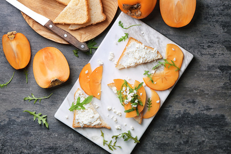 Tasty sandwiches with persimmon and cottage cheese on board