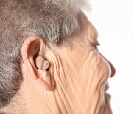 Senior woman with hearing aid on white background Reklamní fotografie - 112783487