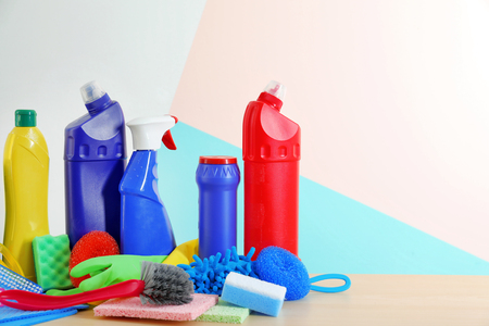 Cleaning supplies and tools on table near color wall Stock Photo