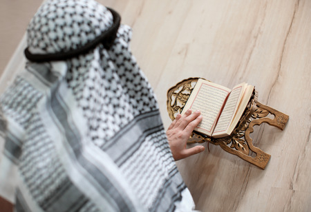 Young Muslim man reading Koran, indoors