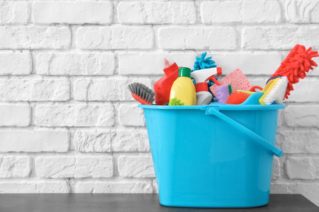 Bucket with cleaning supplies and tools on table near brick wall Stock Photo
