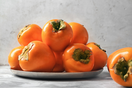 Plate with tasty ripe persimmons on table 스톡 콘텐츠