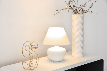 Table with stylish lamp and vase in living room Banque d'images