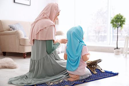 Muslimische Frau betet mit ihrer Tochter zu Hause Standard-Bild