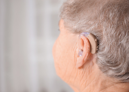 Senior woman with hearing aid indoors
